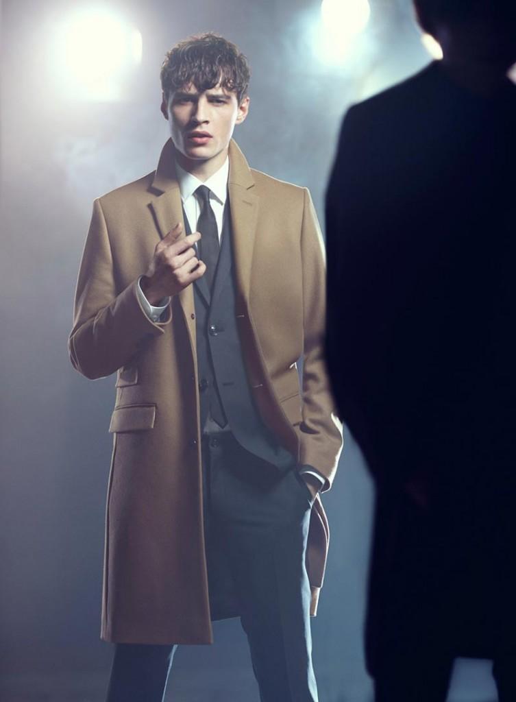 Фото - мужчина-модель в сером костюме и пальто горчичного цвета